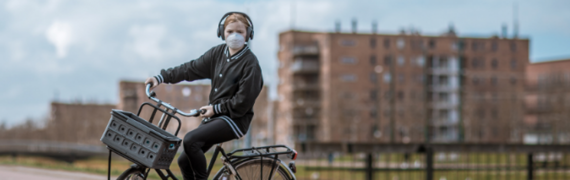Young woman cycling in an urban setting wearing a mask