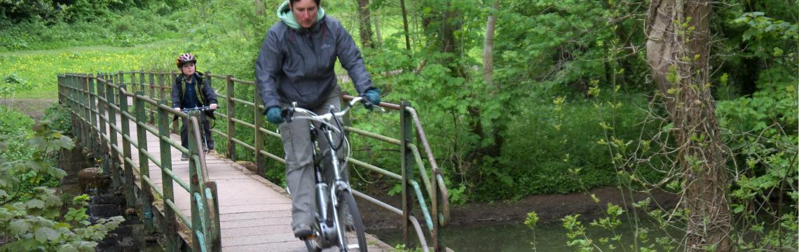 Woman riding over bridge with child in tow