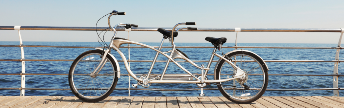 A silver tandem bike parked against the railings of a jetty with the blue sea behind