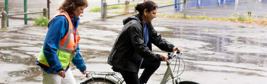 Cycle instructor steadies the white bike of a female, beginner rider