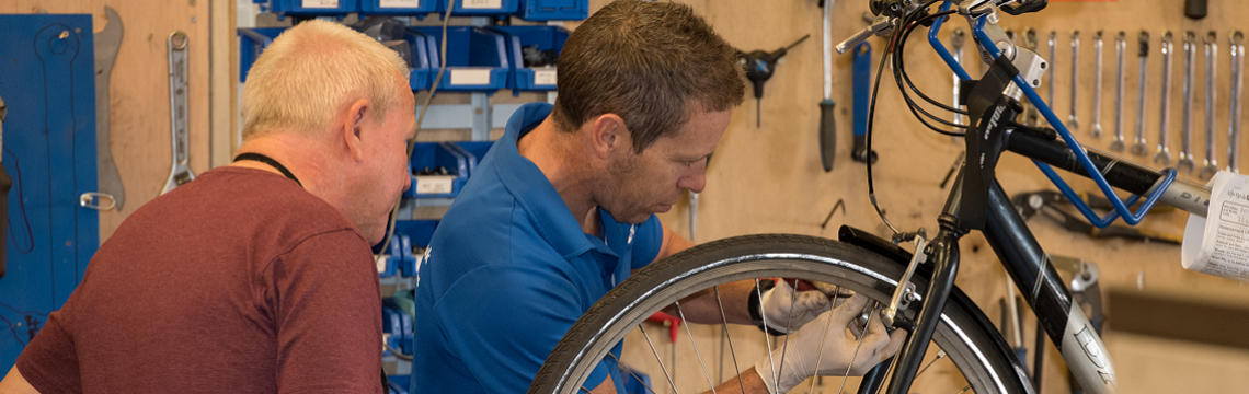 A mechanic and a bike donor look at a donated bike on a rack