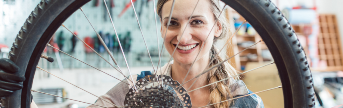 Female mechanic looking through spokes of bike wheel