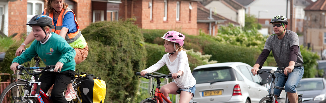 A Life Cycle instructor cycles with a Dad and his kids - a boy and a girl