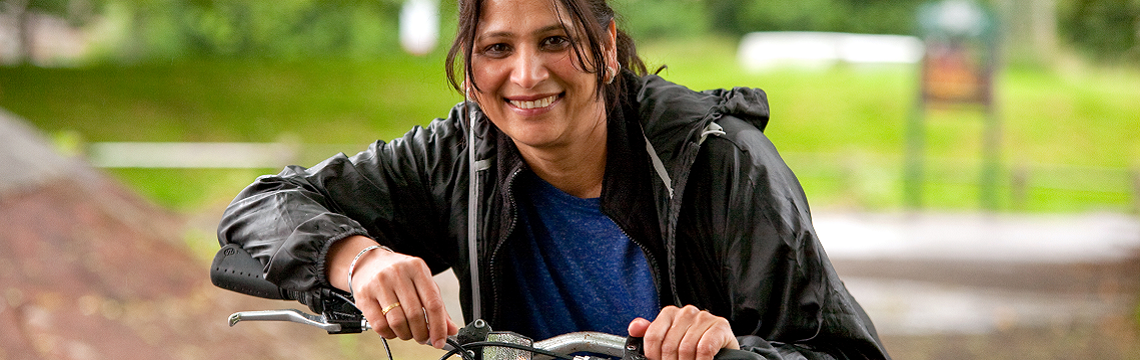 Woman leaning on her handlebars, smiling.
