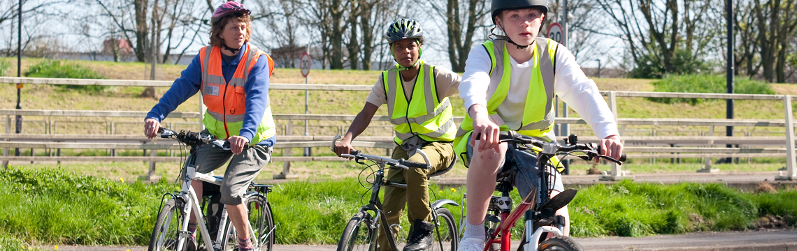 Cycle Instructor riding with two young people in hi-viz jackets