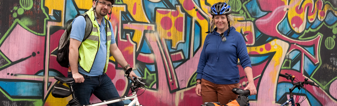 Man and woman with bikes stood in front of wall with graffiti