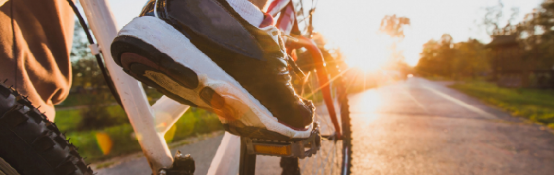Shot from the ground of a man's feet on his pedal with a view down the road into the sunset.