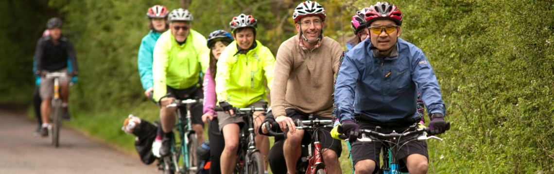 Group of mixed aged and gender cyclists riding in a line on a shared path
