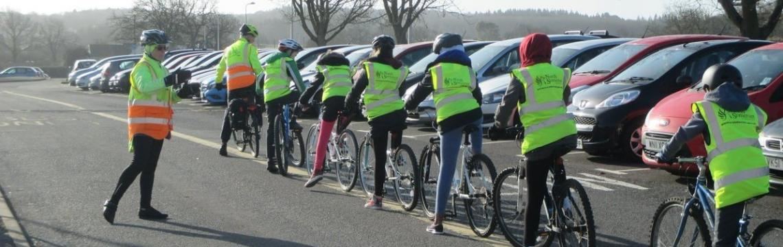 An instructor giving instructions to a line of school children on bikes