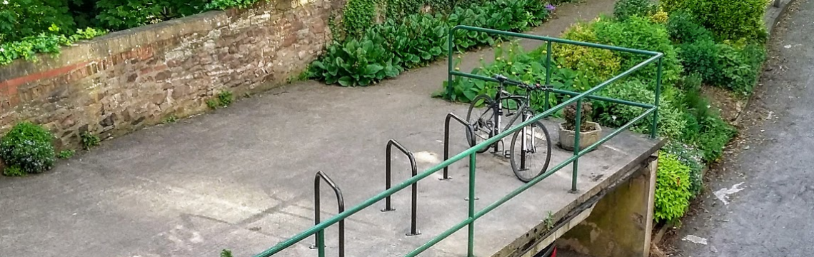 Cycle stands on concrete with bushes