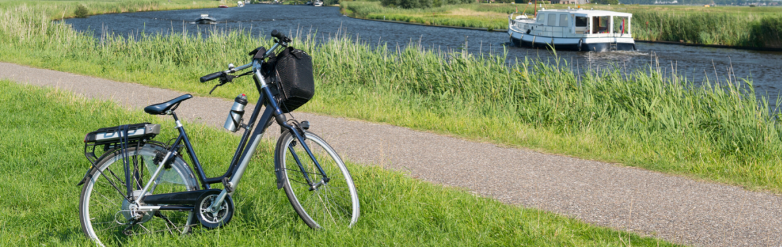 E bike parked on grass near a river.