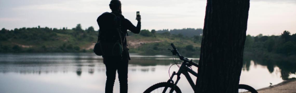 Man bike lake taking selfie with his bike leaning against a tree behind him.