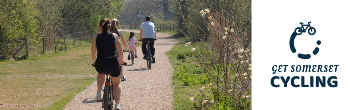 A family cycles away from the camera on a rural cycle path on a summer's day. There is nature all around them and they are wearing summer clothes.