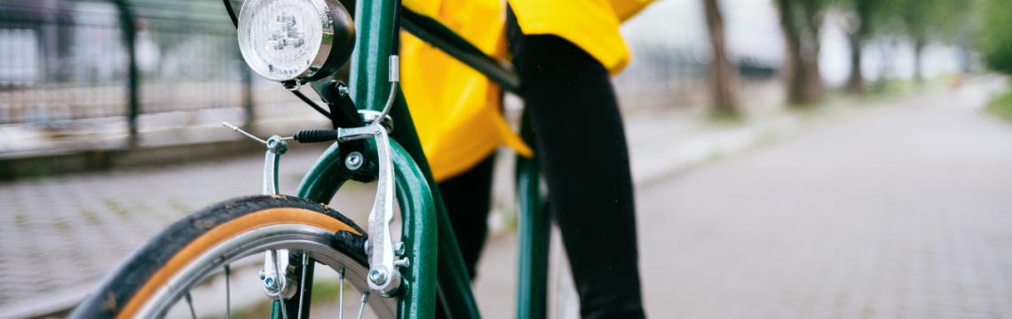 Woman in yellow rain coat on a green bike