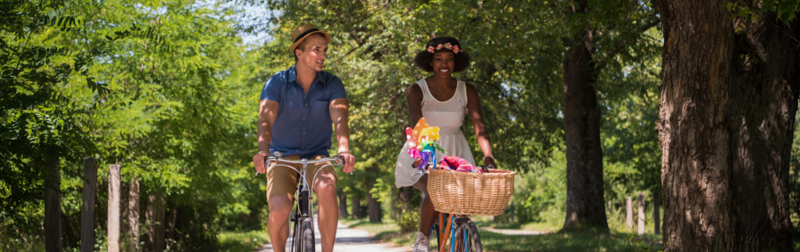 Young man and young woman cycle side by side in summer