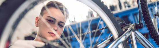 Young lad with short blonde hair looks through wheel spokes