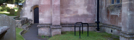 Two black cycle stands in the grounds of an old churh