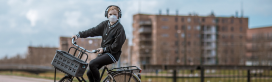 Young woman cycling in an urban setting wearing a mask