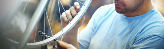 Man in a light blue T-shirt with stubble, working on a wheel without a tire.