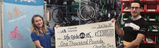 Life Cycle's Becky being presented with a giant cheque by Olly from Chase the Sun