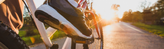 Closeup of a man's feet on the pedals of a bike - he's wearing black and white trainers and you can see the sun is starting to set in the distace