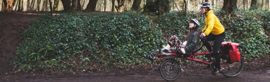 Holly from RORO piloting a 'recumbent tandem' with a female participant on the front